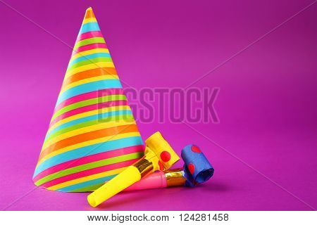 Striped Birthday hat with noise makers on purple background