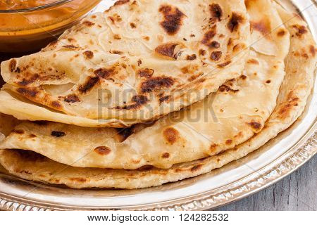 Indian layered Paratha roti kerala porotta with chicken curry on the side