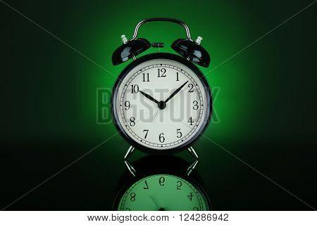 Alarm clock on a dark green background.