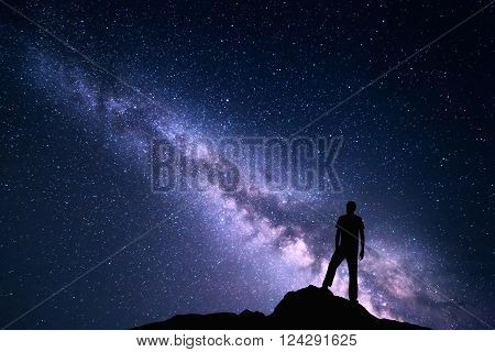 Landscape with purple Milky Way. Night sky with stars and silhouette of a happy man on the stone. Beautiful Universe. Space background