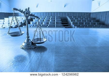 Symbol of law and justice in the empty courtroom law and justice concept focus on the scales. BLUE TONE