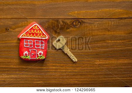 Red sweet house and key on wooden background