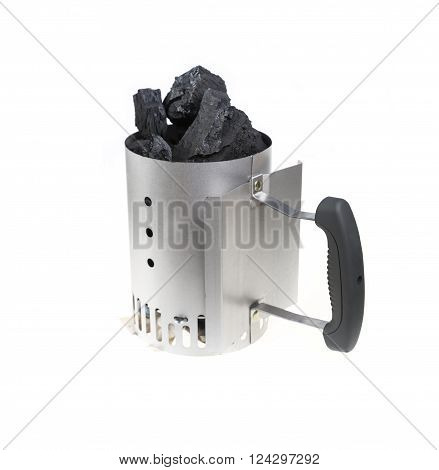 Charcoal chimney starter loaded with natural lump charcoal for BBQ grills.