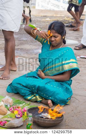 Trichy, India - October 15, 2013: Religious ritual to promote conceiving and pregnancy at Amma Mandapam. Closeup of the woman. Offerings have been made, a flame has been lighted. The woman touches her forehead with an orange, simplified image of a human.