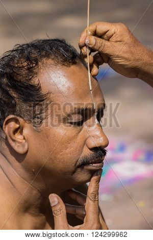 Trichy, India - October 15, 2013: Closeup of man's face while a guru paints the Vishnu symbol in white on the man's forehead at Amma Mandapam. This is part of a religious ritual performed by guru.