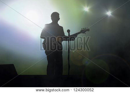 Guitarist on stage performing live under spotlight