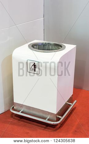 Modern white bin near the conner of exhibition hall.