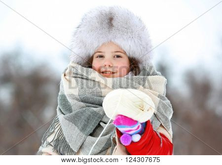 Little girl with winter clothes holding white skein in park outdoor