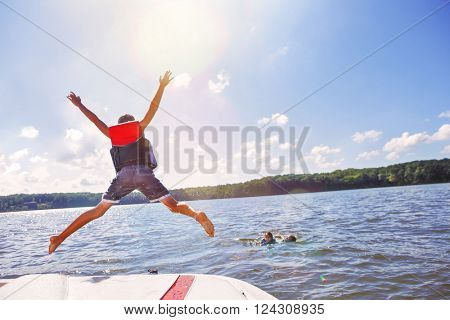 Kids jumping off a boat into the lake. Focus on boys legs and boat, lens flares from sun.
