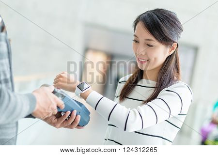 Woman pay by NFC on smartwatch
