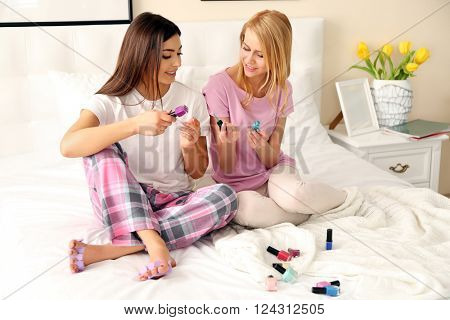 Two girls painting toenails on a bed in living room