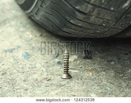 Sharpen metal screw nail nearly to puncture into wheel tire selective focus (colored filter effect)