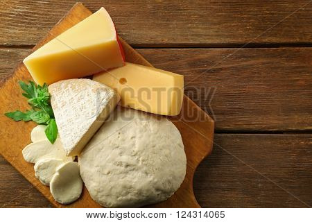 Fresh Italian pizza dough with different kinds of cheese on wooden background