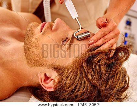 Man gets rejuvenating electric galvanic face spa massage at beauty salon.