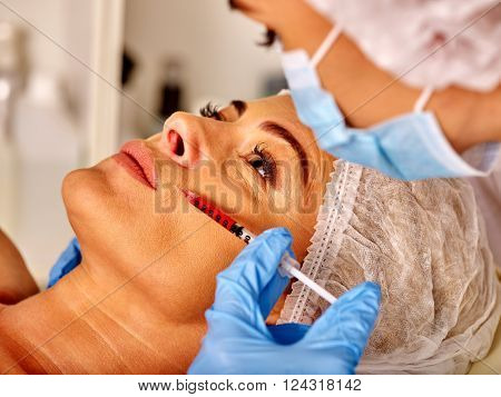 Woman middle-aged into spa salon with beautician in mask. Beauty woman gets rejuvenating injections.