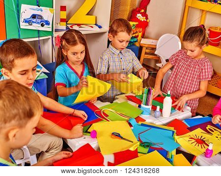Group kids keeps colored paper and glue on table in kindergarten .