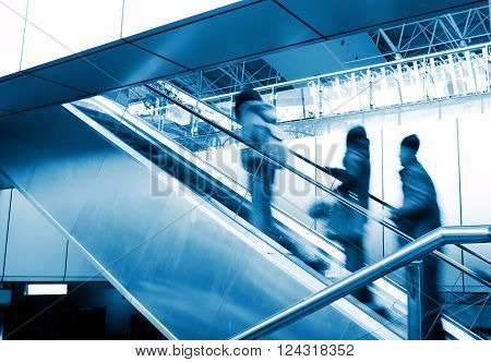 Passengers on the escalator, modern building interior, blue tint FIG.