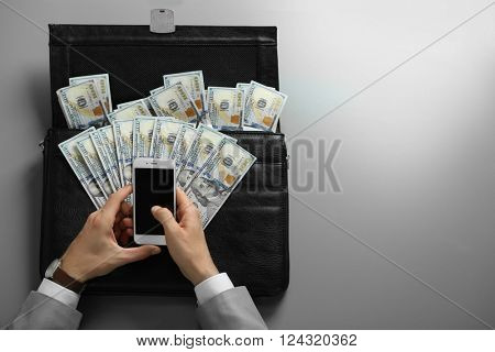 Businessman holding cellphone and brief case with money