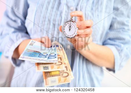 Woman holds money and stopwatch in hands, close up