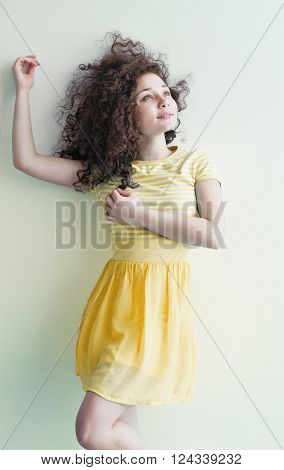 A young girl of Caucasian appearance dancing and dreams of a bright room on a summer day. Wavy curly hair and yellow dress. Rest and be happy.