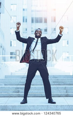 Celebrating success. Full length of happy young African man in formalwear keeping arms raised and expressing positivity while standing outdoors