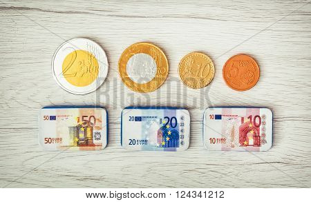 Chocolate money on the wooden background. Euros and cents. Banknotes and coins.