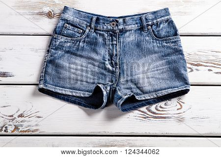 Lady's stylish jeans shorts. Woman's shorts on vintage showcase. Short shorts for teenage girls. Light blue shorts for summer.