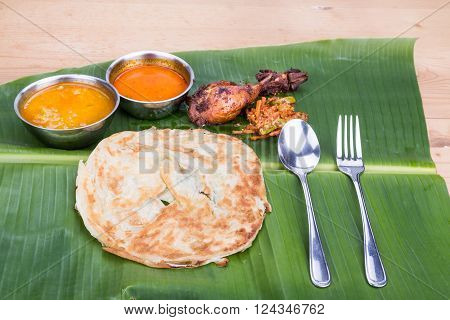 Traditional Roti Prata Served On Banana Leaf With Curry Dhal.