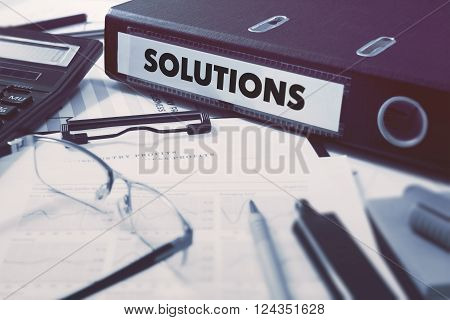 Solutions - Office Folder on Background of Working Table with Stationery, Glasses, Reports. Business Concept on Blurred Background. Toned Image.