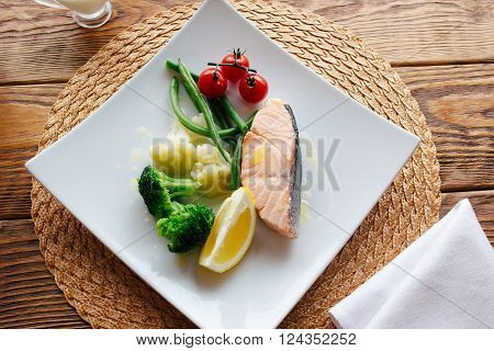 Mediterranean cuisine dish. Salmon steak and steamed vegetables, served on a wooden background. Lenten  healthy Mediterranean cuisine food. Top view on dietary fish dish with salmon and vegetables