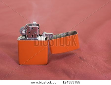 red gasoline lighter with flame on red background poster