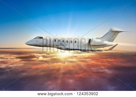 Private jetplane flying above clouds in sunset