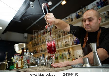 Bartender pouring red cocktail into glass at the bar