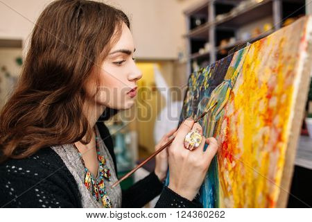 Creative painter paints a colorful picture. Closeup of painting process in art workplace. Painter paints in her studio.