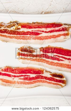 Streaky bacon with on the white plate vertical