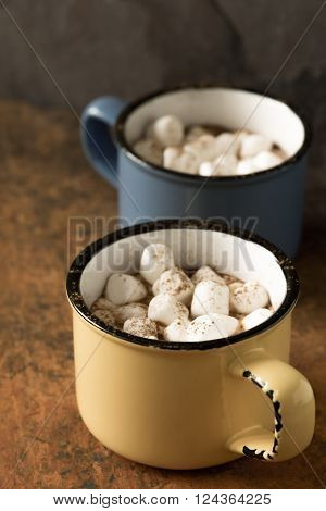 Cups of aromatic cocoa with marshmallows vertical