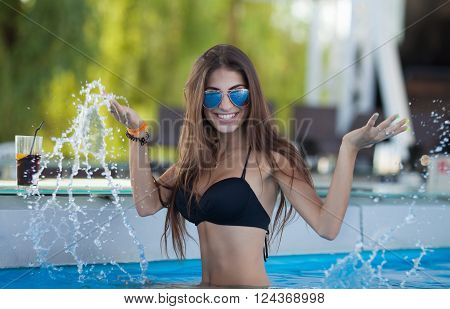 woman taking sunbath near swimming pool. beautiful woman on a tropical beach on a chaise lounge. oung beautiful woman outdoors on the sunbed