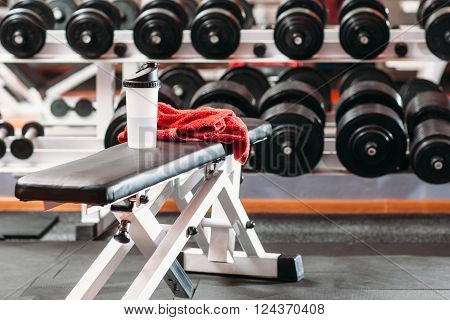 Sport, fitness, healthy lifestyle and bodybuilding concept - close up of bottle with water and wet towel in gym background.  