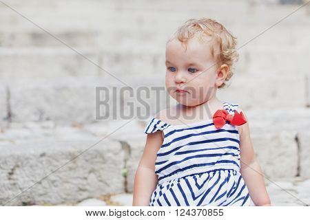 portrait of pensive serious little girl outdoor Italy