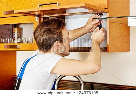 Handyman fixing kitchen's cabinet with screwdriver poster