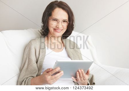 Middle-aged Woman Using Touch Pad Reading A Message, Email Or Information On Her Tablet Computer Sit