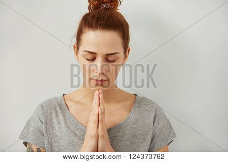 Closeup portrait of a peaceful woman praying. Sad woman prays holding clasp hands together, concept of girl problem, stress, depression. Human emotion facial expression body