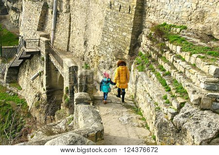 Little girl with mother walking on the along the giant medieval stone wall near fortress of Kamianets-Podilskyi Ukraine