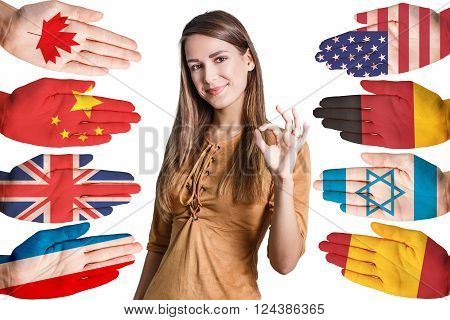 Young woman and many hands with different country flags painted on them isolated on white
