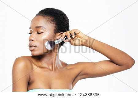 Beautiful afro american woman posing with makeup brush isolated on a white background