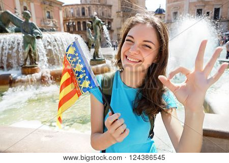 Woman waving Valencian flag happy in Valencia Spain. Smiling cheerful girl having fun in front of Cathedral.