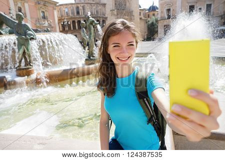 Girl tourist using smart phone camera to take photo while traveling in Valencia Spain. Travel and tourism concept.