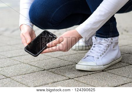 Kneeling Person Picking Up Broken Phone On Street