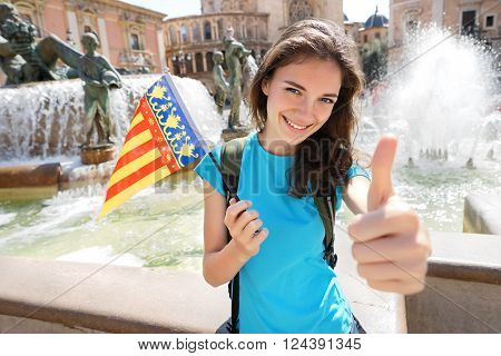 Flag of Valencian Community happy tourist woman in Valencia Spain. Young girl holding flag for holiday vacation concept