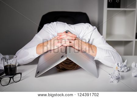 Man having a depression and hiding under laptop